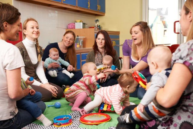 spielende Kinder mit ihren Müttern