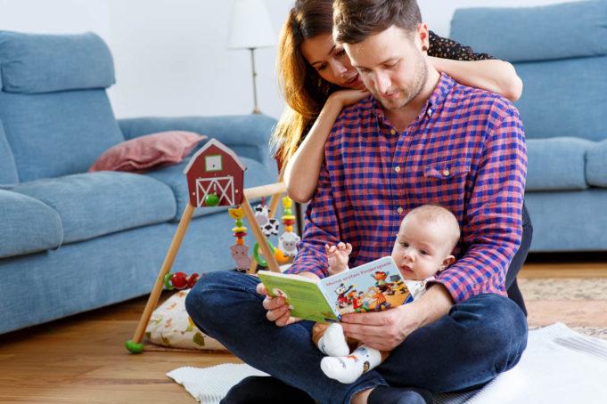 Familie mit Baby und Buch